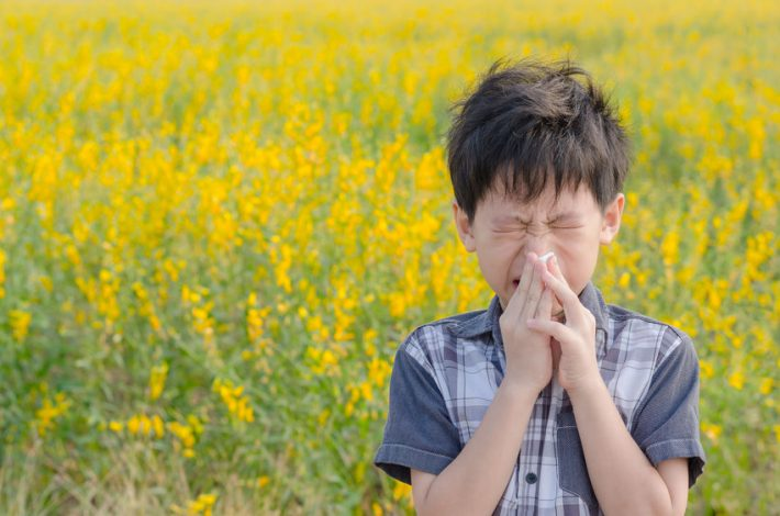Little Asian boy has allergies from flower pollen